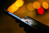 Woman using her mobile phone ,city streetlight background