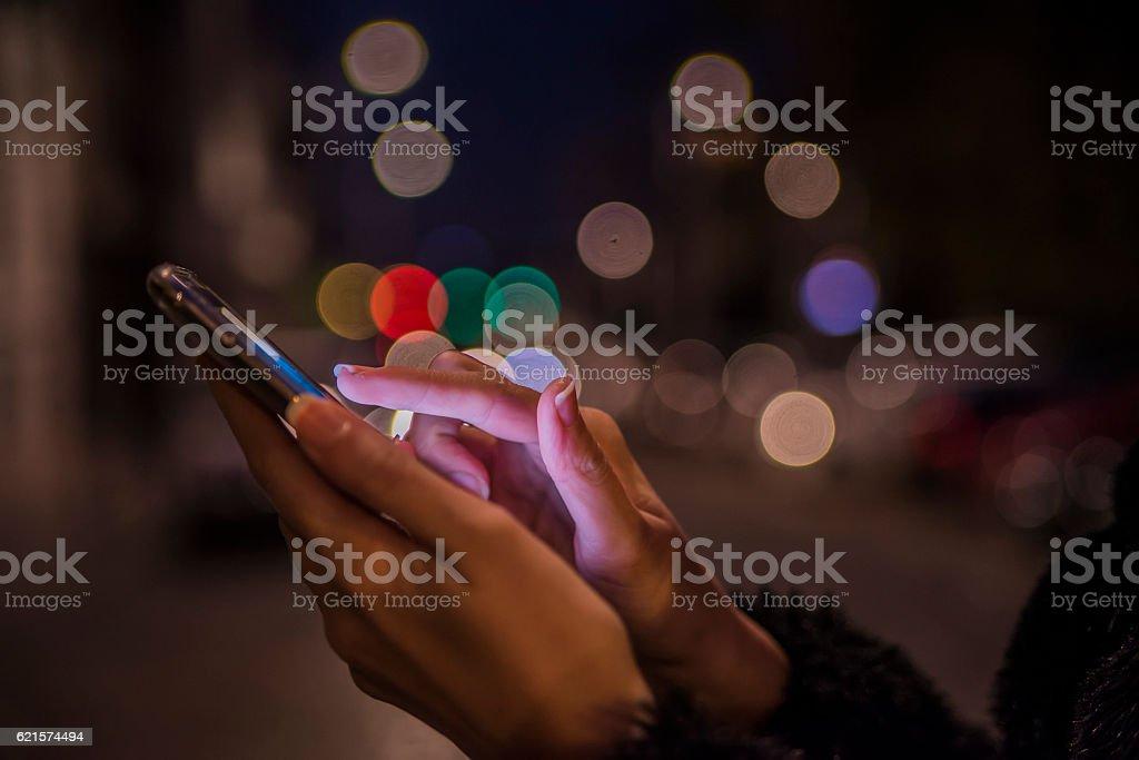 Femme se servant de son téléphone portable, vue sur la ville de nuit héritage photo libre de droits