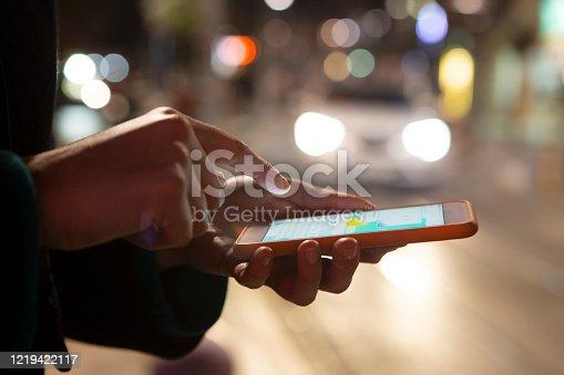 621574390 istock photo Woman using her mobile phone, city skyline night light background 1219422117