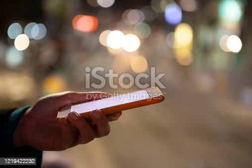 621574390 istock photo Woman using her mobile phone, city skyline night light background 1219422232