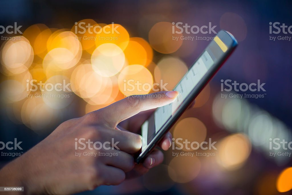 Woman using her mobile phone, city skyline night light background stock photo