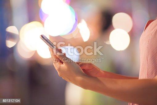 istock Woman using her mobile phone, city skyline night light background 831312104