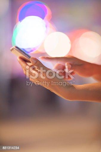 621574390 istock photo Woman using her mobile phone, city skyline night light background 831314234