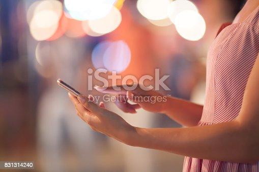 istock Woman using her mobile phone, city skyline night light background 831314240