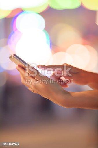621574390 istock photo Woman using her mobile phone, city skyline night light background 831314246