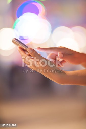 621574390 istock photo Woman using her mobile phone, city skyline night light background 831314292