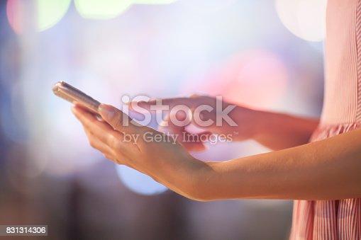 621574390 istock photo Woman using her mobile phone, city skyline night light background 831314306
