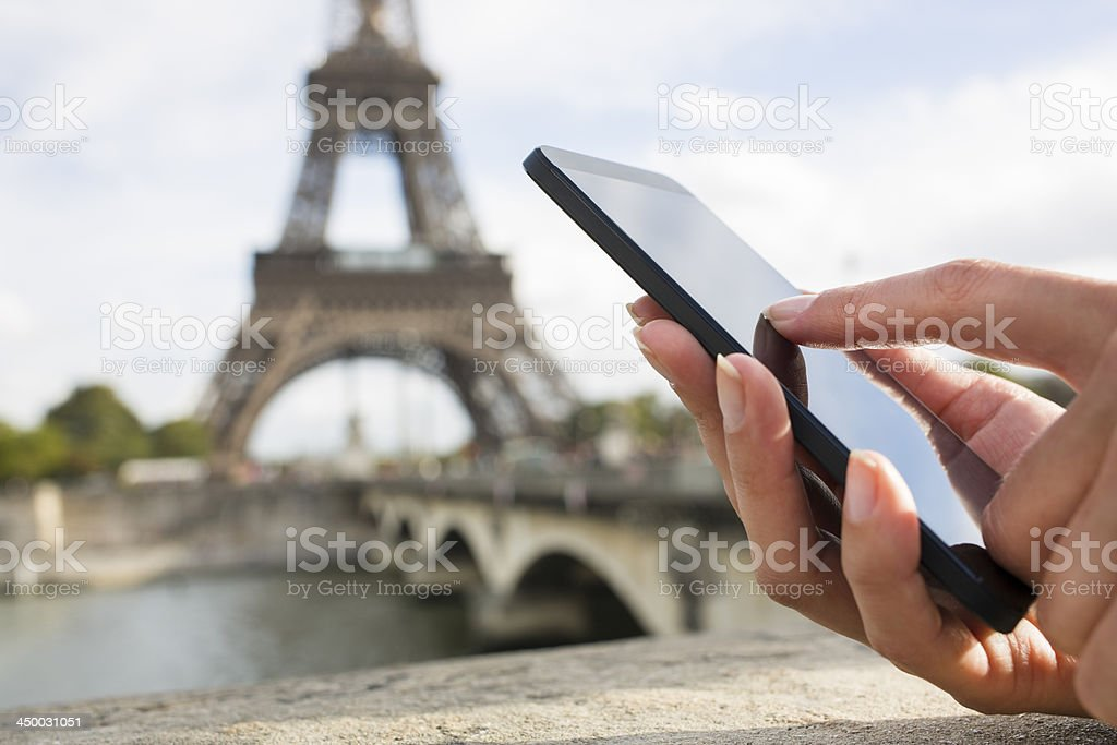 Woman using her Mobile Phone in front of Eiffel Tower stock photo