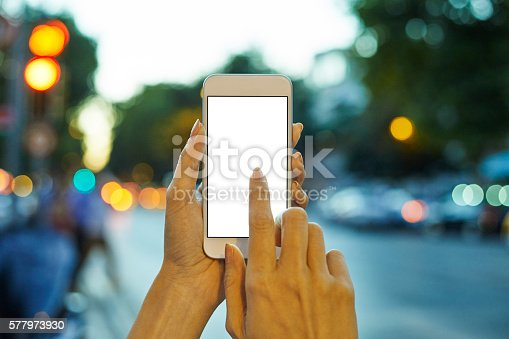 istock Woman Using her Mobile Phone Night Light Background 577973930