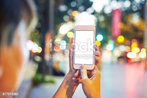 istock Woman Using her Mobile Phone Night Light Background 577974362