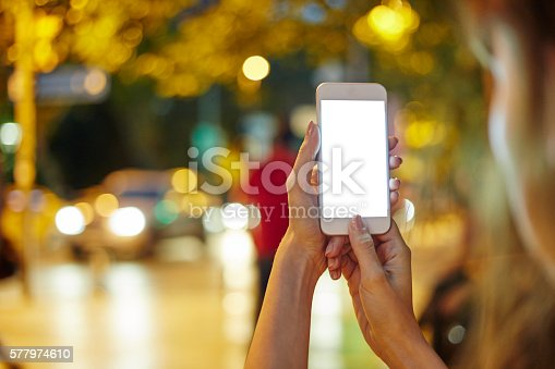 493694506istockphoto Woman Using her Mobile Phone Night Light Background 577974610