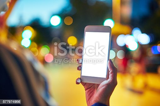 istock Woman Using her Mobile Phone Night Light Background 577974956