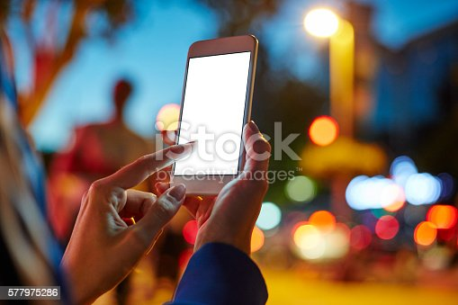 istock Woman Using her Mobile Phone Night Light Background 577975286
