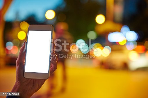 istock Woman Using her Mobile Phone Night Light Background 577975540