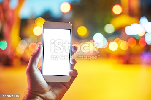 istock Woman Using her Mobile Phone Night Light Background 577975846