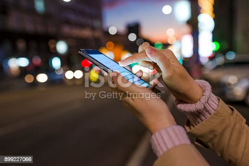 622971132istockphoto Woman using her mobile phone, night light background 899227066