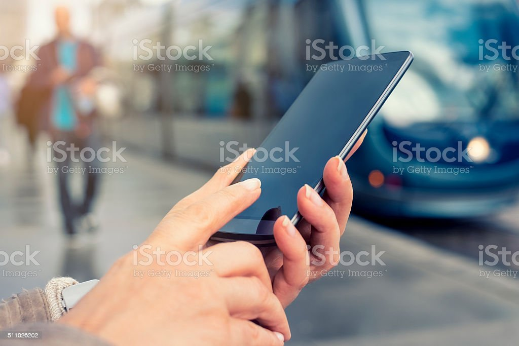 Woman using her mobile phone on tramway platform station stock photo