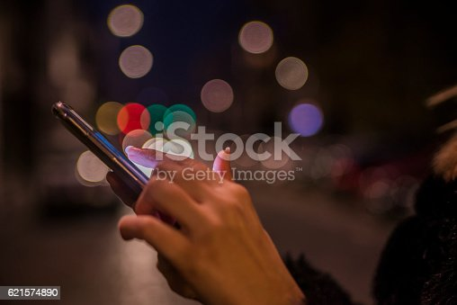 istock Woman using her Mobile-Phone in the street, night light Background 621574890
