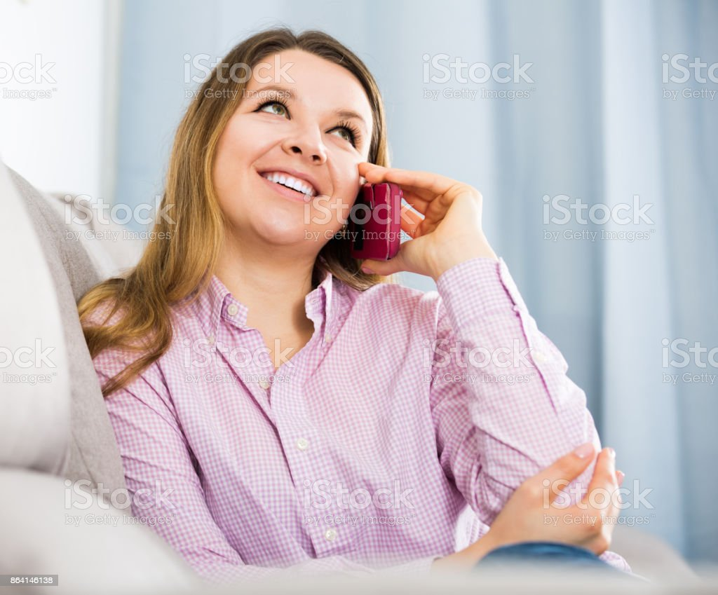 Woman using her phone and smiling royalty-free stock photo