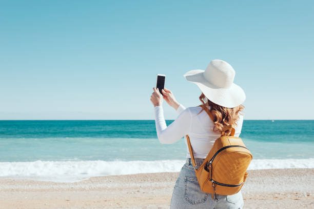 Woman using her phone at the beach stock photo