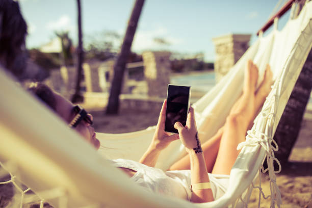 mujer utiliza su teléfono mientras se relaja en una hamaca - mujeres dominicanas fotografías e imágenes de stock
