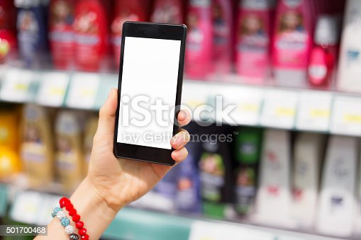 1184048369 istock photo Woman using her smartphone in supermarket 501700468