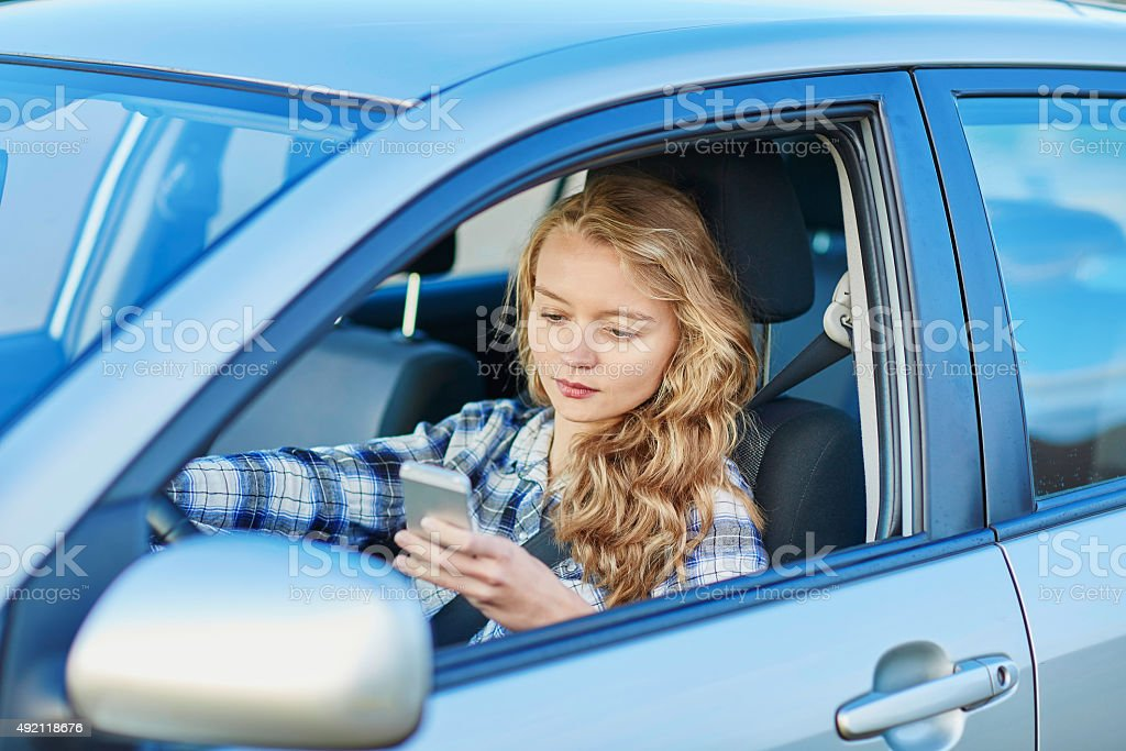 Woman using her smartphone while driving a car stock photo