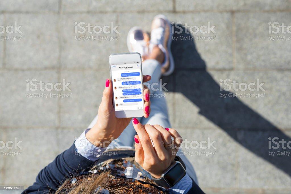 Mujer mediante la aplicación de mensajería instantánea en el teléfono móvil foto de stock libre de derechos