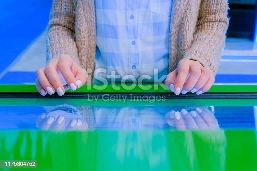 Education and technology concept - woman using interactive touchscreen display of green electronic kiosk at technology exhibition or museum
