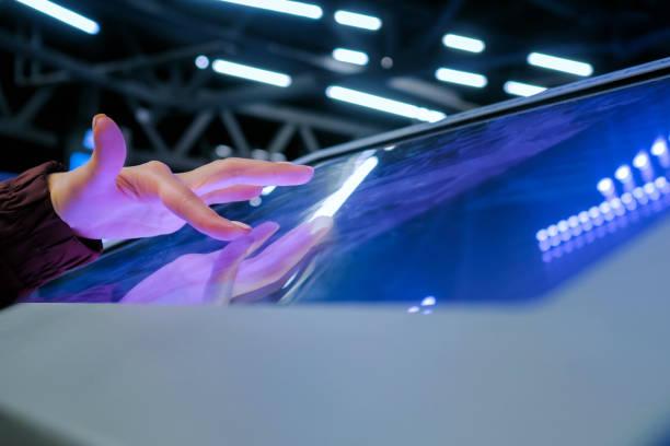 femme utilisant l'affichage interactif d'écran tactile à l'exposition de technologie - écran tactile photos et images de collection