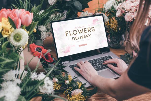 femme en utilisant l'interface de fleuriste - fleuriste photos et images de collection