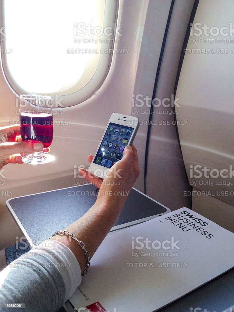 Woman using iPhone 4s on board of Swiss Airlines plane stock photo