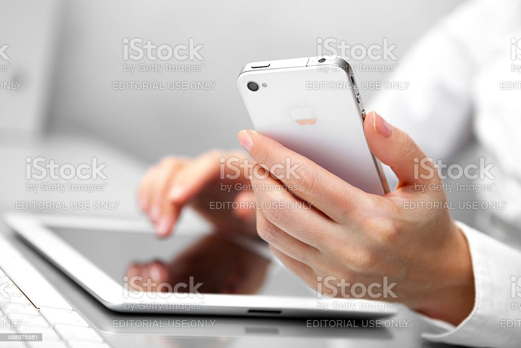 Woman Using iPhone and iPad royalty-free stock photo