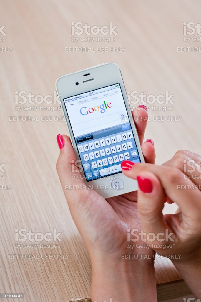 Woman using Iphone4 with Google application royalty-free stock photo