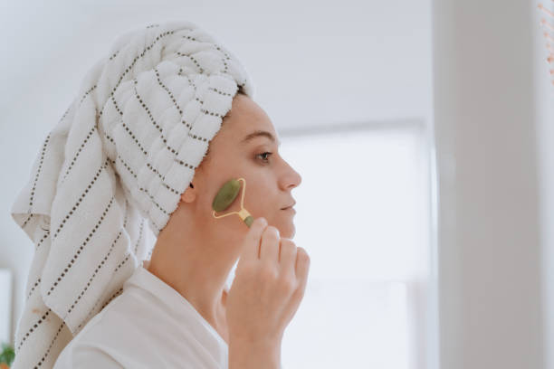 Woman using jade roller on her face at home stock photo