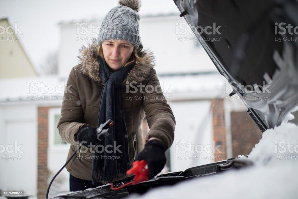 Frau mit Überbrückungskabel auf Autobatterie an verschneiten Tag – Foto