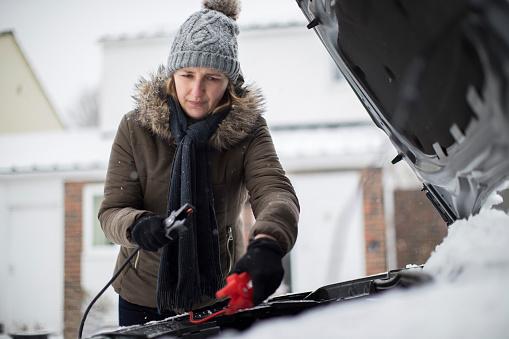 Frau Mit Überbrückungskabel Auf Autobatterie An Verschneiten Tag Stockfoto und mehr Bilder von Auto