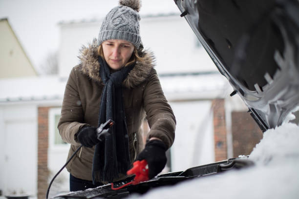 woman using jumper cables on car battery on snowy day - car chill foto e immagini stock