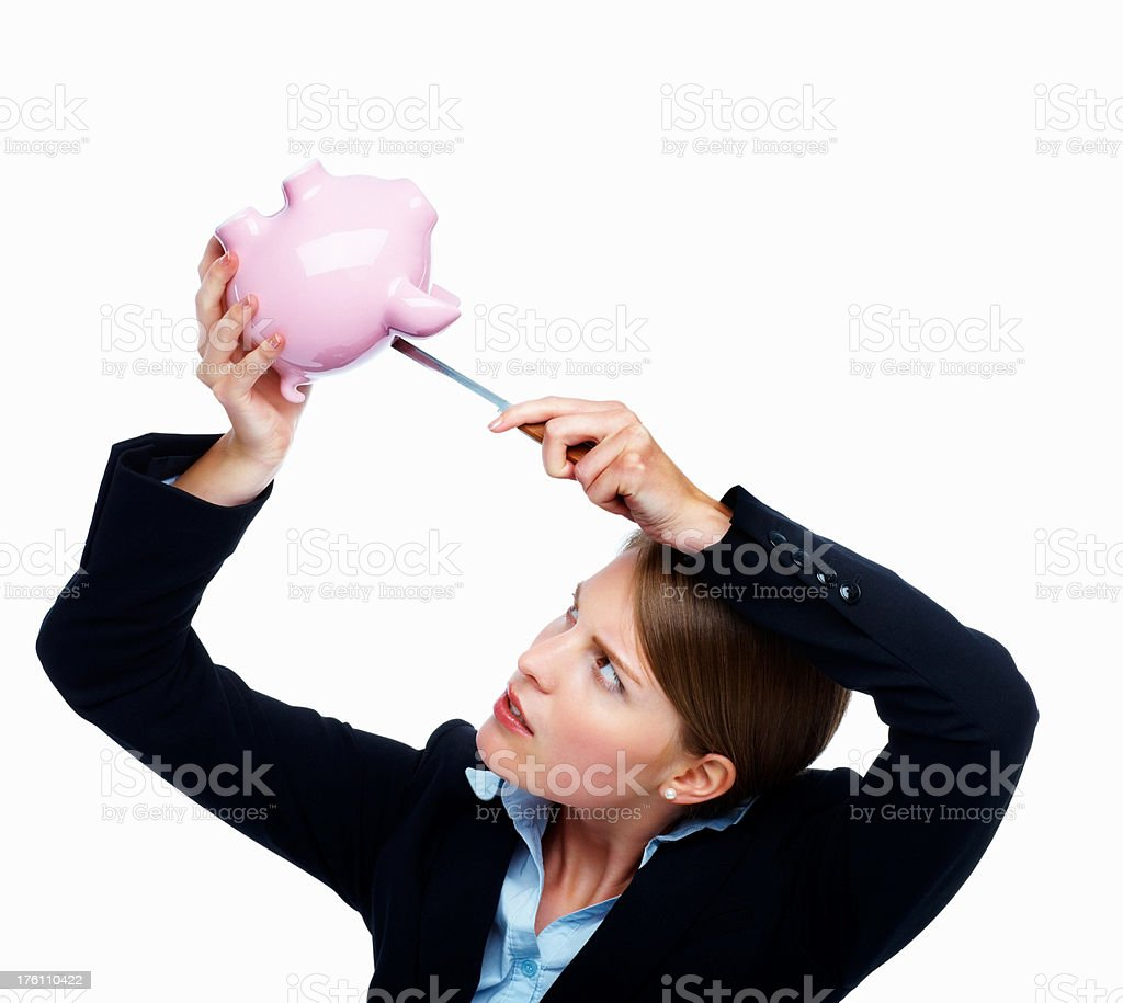 Woman using knife to remove money from a piggybank royalty-free stock photo