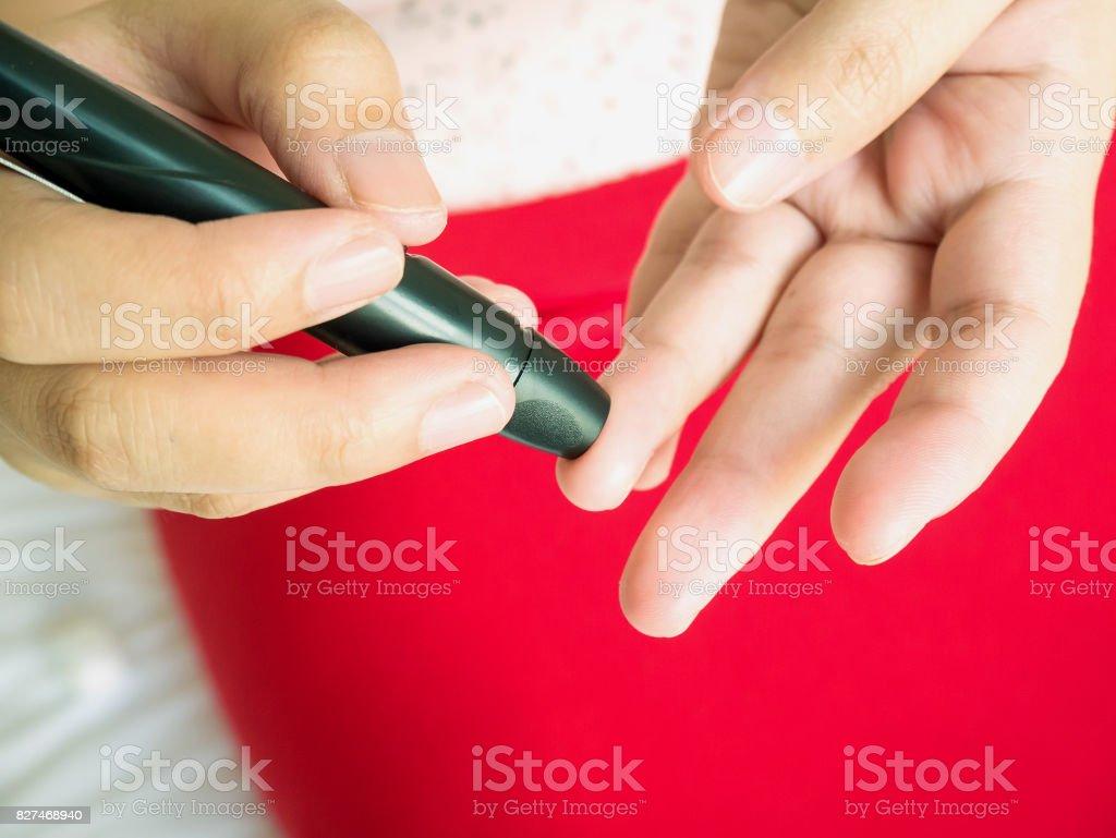 woman using lancelet on finger, diabetes test stock photo