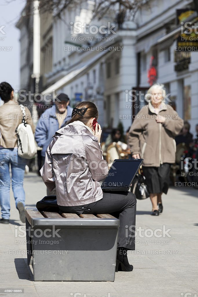 Woman using laptop and cell phone outdoors. stock photo