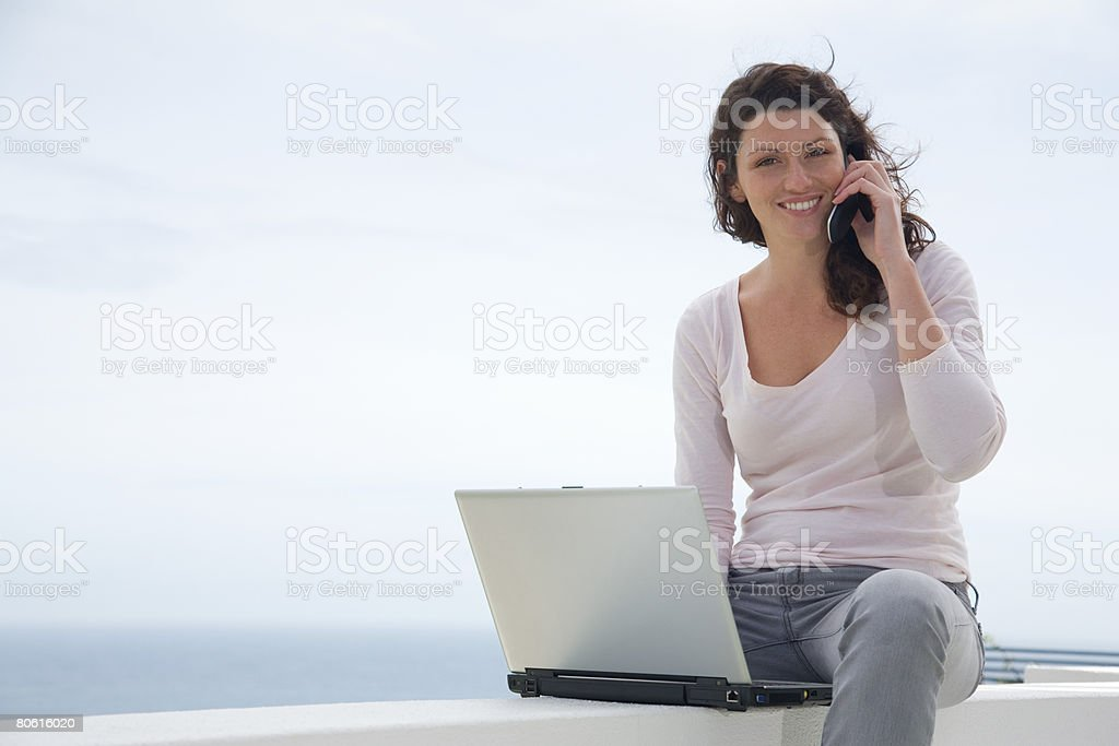 Woman using laptop and cell phone royalty-free stock photo