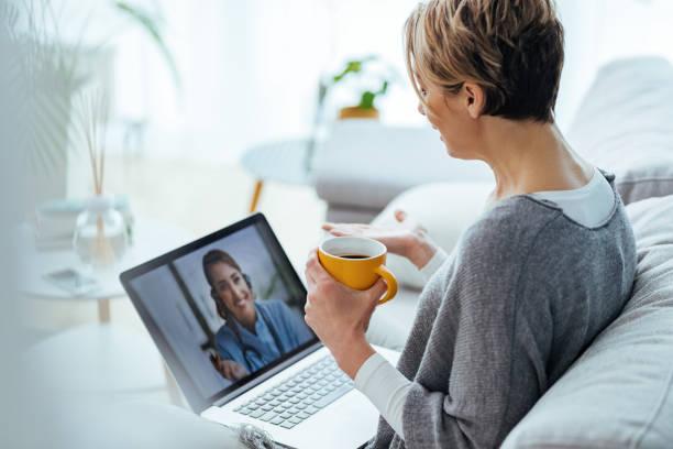 mujer usando computadora portátil y haciendo videollamada con su médico mientras estaba sentada en casa. - telehealth fotografías e imágenes de stock