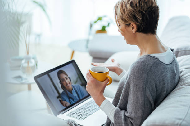 Woman using laptop and having video call with her doctor while sitting at home. stock photo