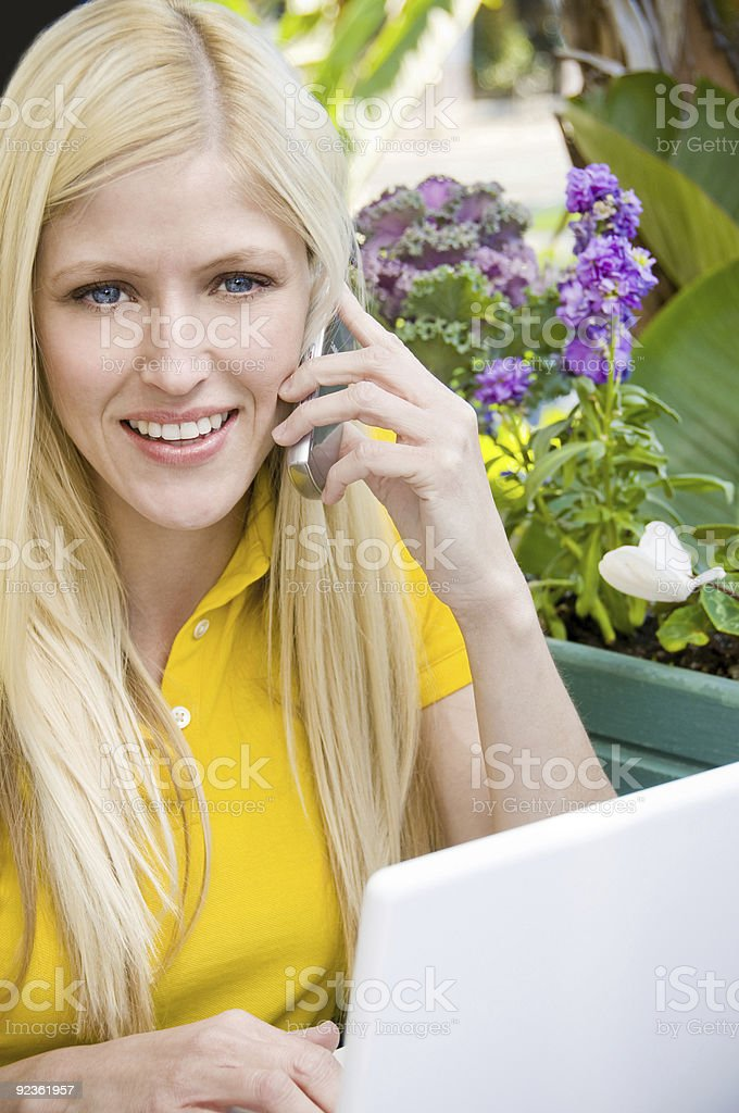 Woman using laptop and talking on cell phone royalty-free stock photo