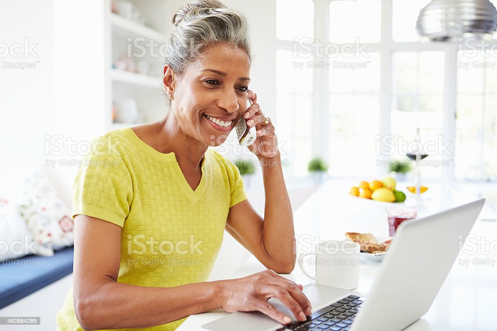 Woman Using Laptop And Talking On Phone At Home stock photo
