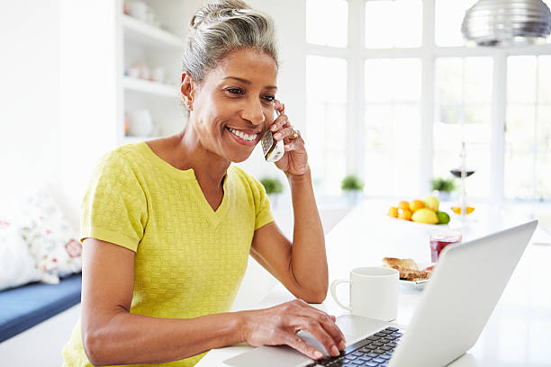 woman using laptop and talking on phone at home - older woman phone stock photos and pictures