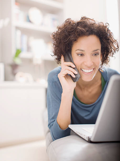 Woman using laptop and talking on telephone  cordless phone stock pictures, royalty-free photos & images