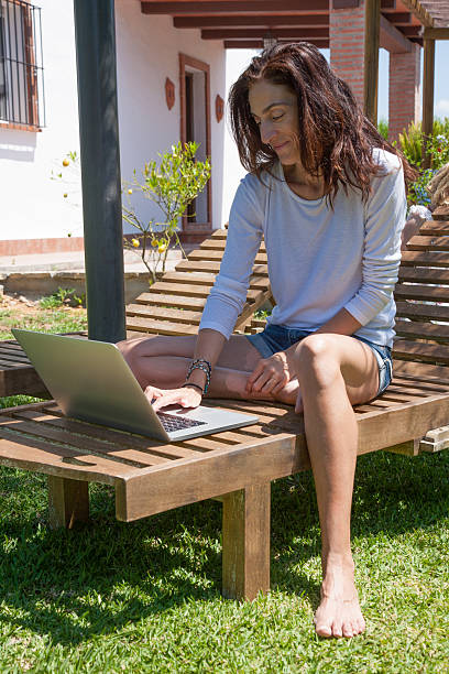 woman using laptop at garden stock photo