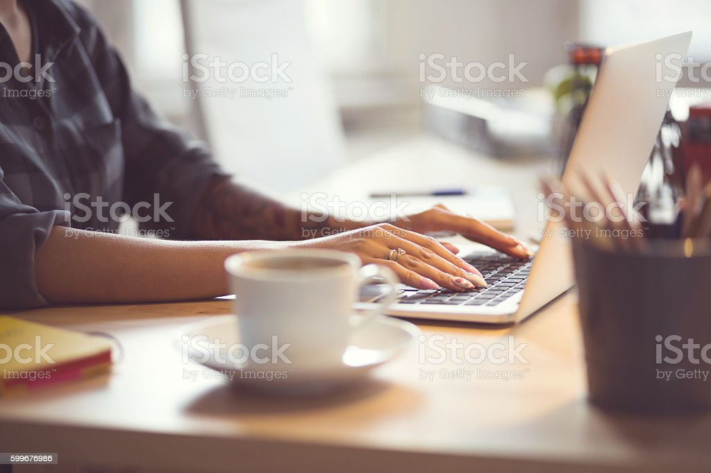 Woman using laptop at home, close up of hands Woman sitting at the desk and using a laptop in an office or at home, close up of hands, unrecognizable person. Adult Stock Photo